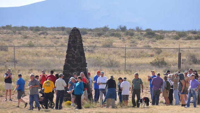 Visitors walk around the Trinity Site obelisk that was declared a landmark in 1975.