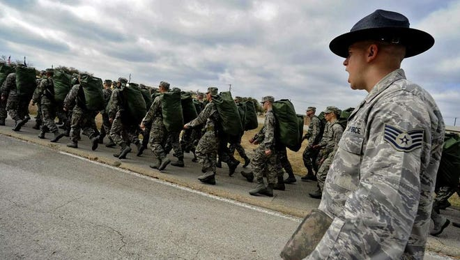 Staff Sgt. Robert George, a TI at Lackland Air Force Base marches his unit following the issuance of uniforms and gear.