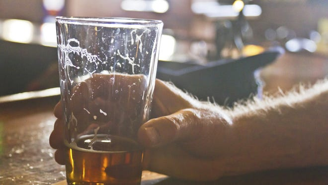 In this photo, a glass of alcohol is set down at a bar.