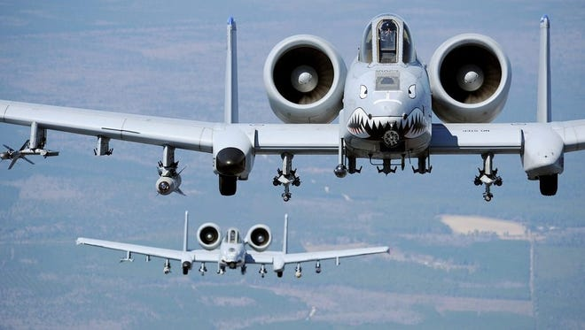 Two A-10C Thunderbolt II aircraft from the 74th and 75th Fighter Squadrons fly behind a HC-130P/N Combat King from the 71st Rescue Squadron during a flight training session here March 16. The A-10C is the first Air Force aircraft specially designed for close air support of ground forces.