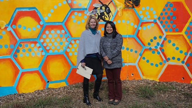 Warren Wilson College President Lynn Morton and professor Lara Nguyen dedicated the new Owen Middle School mural, which adorns the retaining wall behind Owen Pool, on Oct. 25.