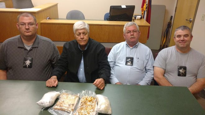 Five pounds of methamphetamine are on display in front of (from left) Lt. Charlie Melton, Sheriff Jack Yancey, chief deputy Earnie Blackley and Sgt. Gabe Sanders of the Izard County Sheriff's Office following recent drug busts.