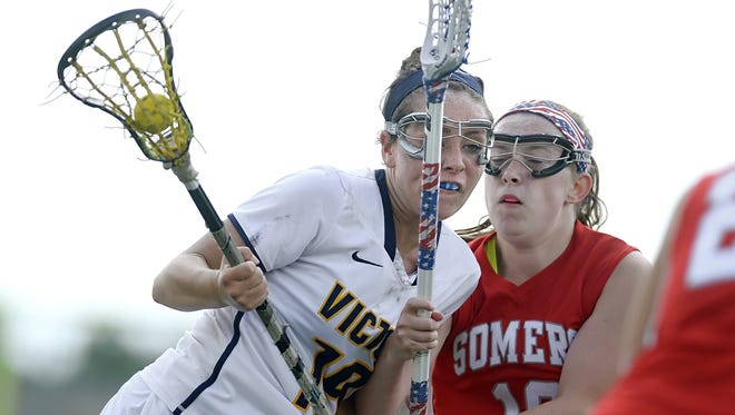 Victor's Bridget Flynn, left, is challenged by Somers' Christine Olert during the NYSPHSAA Girls Lacrosse Championships Class B semifinal played at SUNY Cortland on Friday, June 5, 2015. Victor's season ended with a 14-8 loss to Somers-I.