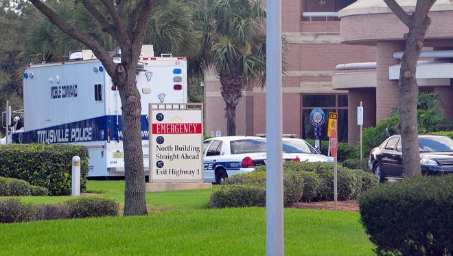 Titusville Police Department's mobile command unit and other police vehicles park outside Parrish Medical Center following last Sunday's fatal shootings of a hospital patient and an employee.