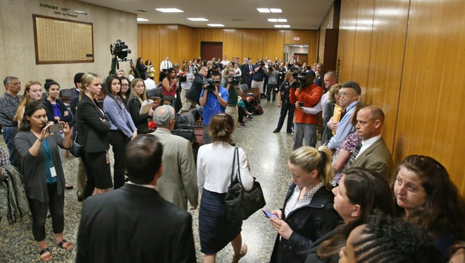 THE PHOTO: Laura Rideout, bottom center in white sweater, walks with her lawyers, Michael DiPrima, left, and David Pilato, bottom, past a crowd of onlookers and media as they head into court for the verdict in the Craig Rideout murder trial.