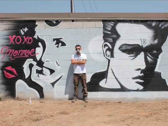 A.J. Gomez stands with his Hollywood-inspired mural on display in Parlier.