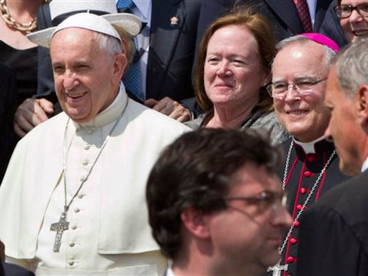 Philadelphia's Archbishop Charles Chaput, right, stands next to Pope Francis as they pose for a photo with a delegation from Philadelphia at the end of the pontiff's weekly general audience in St. Peter's Square at the Vatican in June.