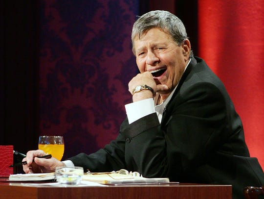 Jerry Lewis laughs while watching a performer during