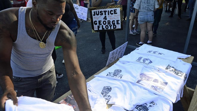 Jerome Gunn lays t-shirts out on a table at the beginning of a march in support of justice for George Floyd in Alabama City on Sunday. More local protests are scheduled for Saturday.