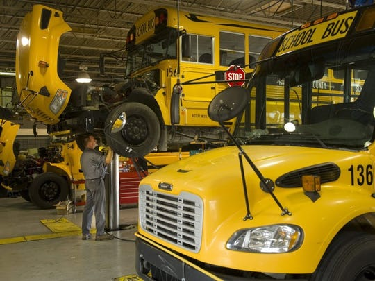 Brian Vandiver checks the fluid levels of a Bluebird school bus in preparation for the new Henderson County school year Friday afternoon.