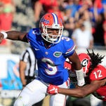 Treon Harris (3) of the Florida Gators is pressured by Juwuan Briscoe (12) of the Georgia Bulldogs during the game at EverBank Field on October 31, 2015 in Jacksonville.