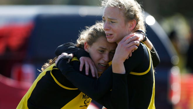 Mid-Prairie sophomore Marie Hostetler (right) holds sister Anna Hostetler Saturday, Oct. 28, 2017, as the two are overcome with emotion after finishing first and second in the 2A girls race at the State Cross County Championships in Fort Dodge.