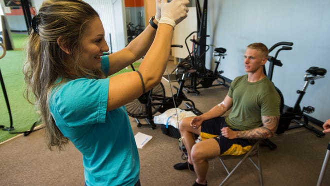IV Rehab lead technician Faith Yunger squeezes the IV bag while administering an athletic recovery IV treatment to client Ben Alexander on Monday, July 9, 2018, at Vigor Performance in Loveland, Colo.