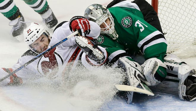 Devils right wing Kyle Palmieri (21) slides into Dallas Stars goalie Antti Niemi during the third period of Tuesday night's game in Dallas. The Devils won in 2-1 in overtime.