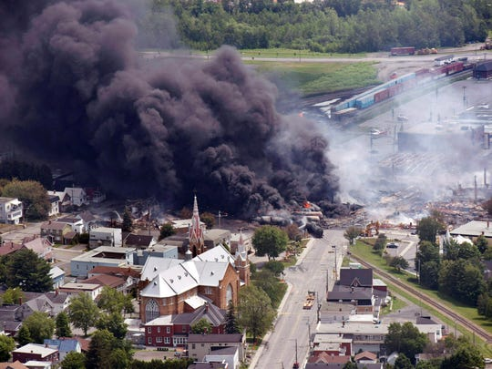 In this July 6, 2013, file photo, smoke rises from railway cars from now defunct Montreal, Maine & Atlantic Railways company that were carrying crude oil after derailing in downtown Lac Megantic, Quebec, Canada.