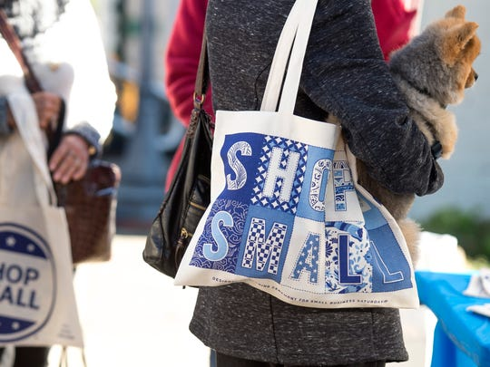 """Virginia Zeeb, right, of St. John, Mo., holds her dog Sammy while they talk to the executive director of Historic Newburgh, Inc. during Small Business Saturday in downtown Newburgh, Ind., on Saturday, Nov. 25, 2017. Historic Newburgh, Inc. handed out free tote bags that read """"shop small"""" for Small Business Saturday."""