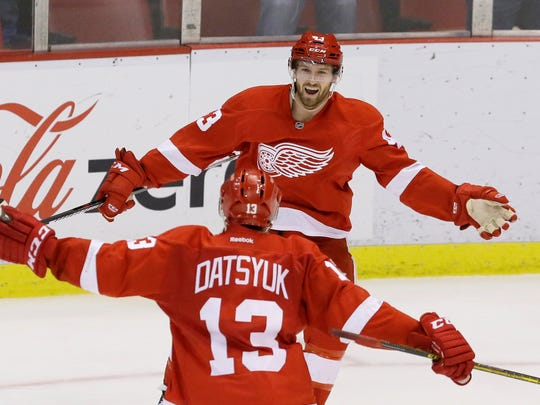 Detroit Red Wings center Darren Helm is congratulated by teammate Pavel Datsyuk after scoring in overtime to beat the New York Rangers, 3-2, Saturday, March 12, 2016, in Detroit.