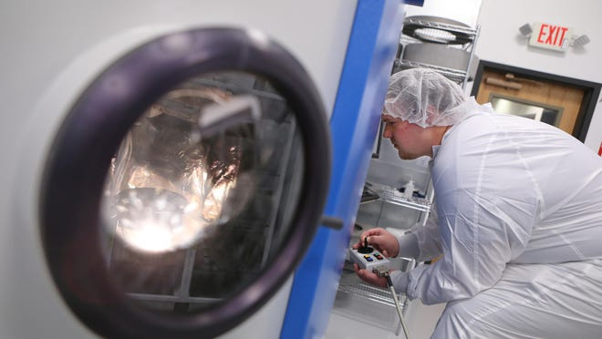 Coating technician David Pike works in a clean room at Optimax in Ontario, Wayne County.