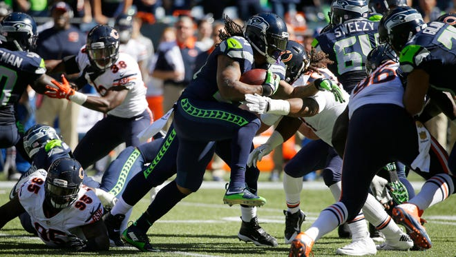 Seattle Seahawks running back Marshawn Lynch, center, rushes against the Chicago Bears in the first half of an NFL football game, Sunday, Sept. 27, 2015, in Seattle.