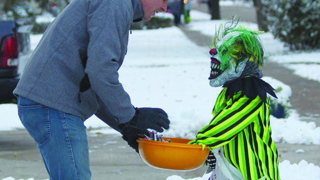 A Prospect Street resident hands out candy during last year's snowy Halloween event.