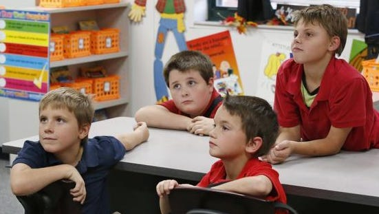 From left, Junior Bowersock, 8, Bryan Bowersock, 11, C.J. Bryson, 7 and Kyle Warren, 12, listen to their teacher during a New Hope after-school program at Mark Twain Elementary School, on Oct. 21, 2015, in Tulsa, Okla. New Hope Oklahoma offers after-school programs, weekend retreats and overnight summer camps that annually serve about 500 children who have a parent in prison.