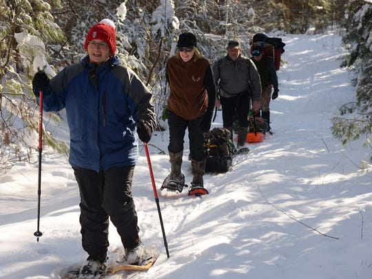 Karen Watson, Brenda Maier, John Maier and Tim Watson snowshoe toward a distant lake for a day of ice fishing in northwestern Wisconsin.