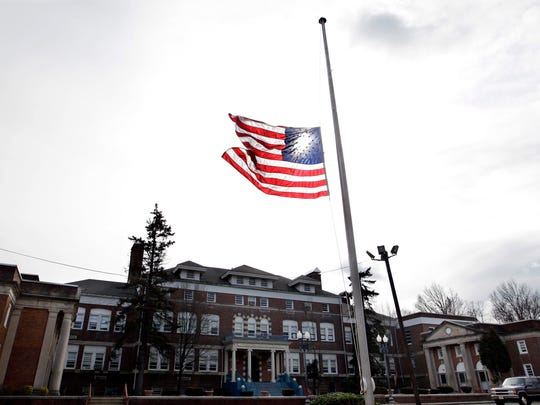In this Feb. 12, 2012 file photo, an American flag flies at half-staff in front of the Whitney E. Houston Academy of Creative and Performing Arts in East Orange to honor the performing artist Whitney Houston, who died the previous day. The honor once reserved for slain police officers, politicians and war heroes is more commonly extended to sports heroes and entertainers.