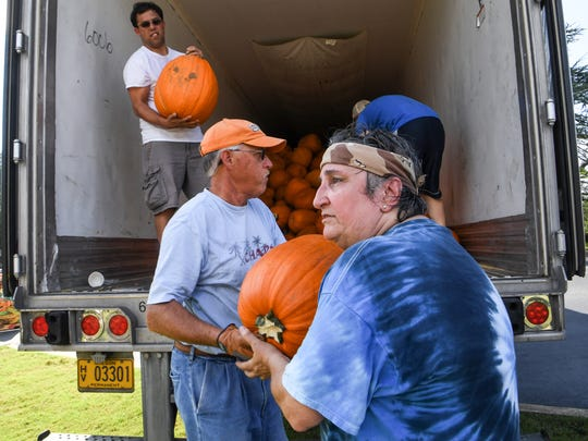 Caroline Brashear, right, a member of Trinity United Methodist Church in Anderson, leads the assembly line of volunteers unloading over 2,600 pumpkins from New Mexico for the church pumpkin patch in Anderson on Wednesday. Trinity selected recipients of this year's funds for Anderson Interfaith Ministries, Boy Scouts, Cancer Association of Anderson, Costa Rica Missions, Family Promise, Offer's Christian Fellowship, Parkinson's Association of Anderson, and the Weekend SnackPack program.