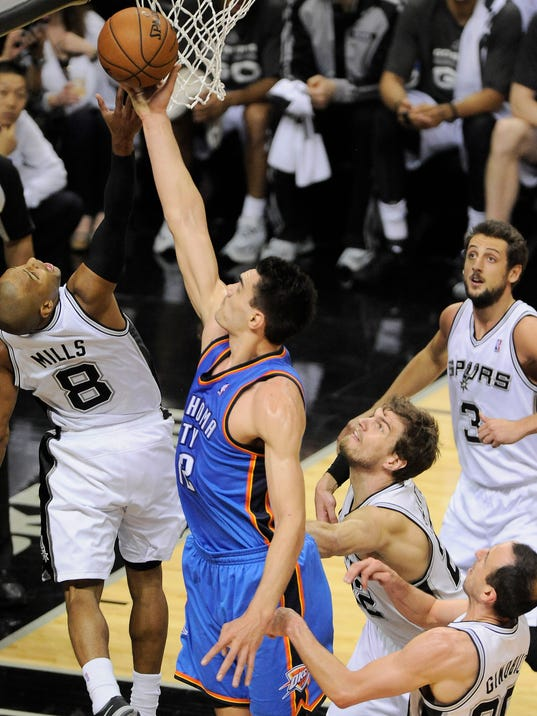 Oklahoma City Thunder center Steven Adams, center, shoots against San Antonio Spurs guard Patty Mills, left, of Australia, as Spurs' Marco Belinelli, top right, of Italy, Manu Ginobili, bottom right, of Argentina, and Tiago Splitter, of Brazil, help on defense during the second half of Game 5 of the NBA basketball Western Conference finals, Thursday, May 29, 2014, in San Antonio. San Antonio won 117-89. (AP Photo/Darren Abate)