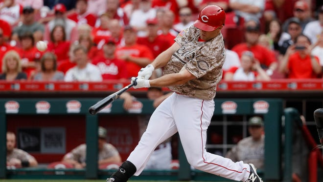Cincinnati Reds' Scott Schebler hits a go-ahead three-run home run off Colorado Rockies relief pitcher Mike Dunn in the sixth inning Saturday.