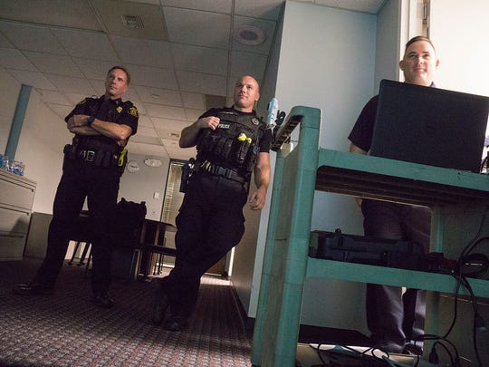 Franklin Police Officer Brian Crane, Farmington Police Officer Scott Brown and Farmington Hills Police Sgt. Brian Bastianelli review a training scenario.