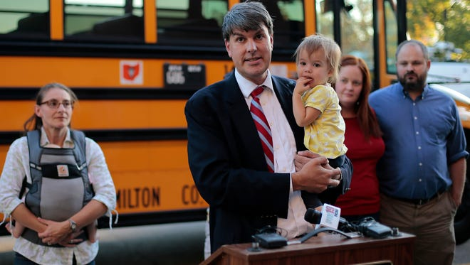 Jeff Cramerding holds his 1-year-old daughter, Maura, as he speaks to the media during a press conference in front of the Cincinnati Public Schools headquarters in Corryville on Sept. 21. The Cincinnatians for School Access group of parents rented a school bus to travel together and protest changes to CPS' magnet enrollment program at the weekly board meeting.