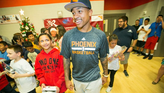 Phoenix Suns point guard Isaiah Thomas meets with children at the Jerry Colangelo Branch of the Boys and Girls Clubs where they collected autographs and presents in Phoenix on Monday, December 22, 2014.