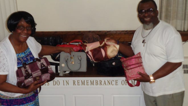 Lady Rose Simpson, left, and her husband, Bishop Larry Simpson, sort through purses donated for the Purses with a Purpose program at New Heights Ministries International.