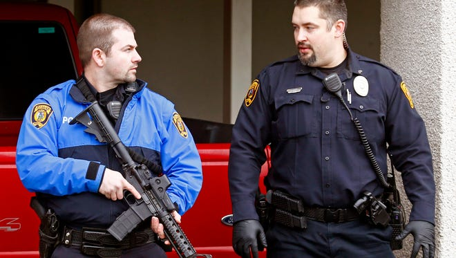 Police officers talk outside while emergency medical technicians aid one of the shooting victims in Moscow, Idaho, on Saturday, Jan. 10, 2015. Police say a gunman killed three people and critically wounded another during a spree at three locations in Moscow, Idaho.
