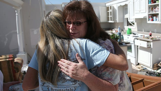 Alice Simpson (R) gives a comforting hug to Cherie Bell as she visits her as she helps her parents salvage items from their home that was damaged on Monday by a tornado on April 30, 2014 in Louisville, Miss.