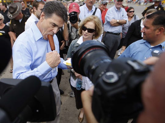 Texas Gov. Rick Perry chomps on a corn dog as he makes his way up the Grand Concourse at the 2011 Iowa State Fair.