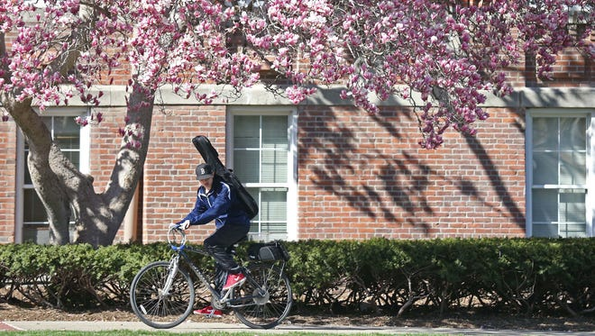 A biker rides past magnolia trees in bloom outside of Old Main on the Drake University campus on Monday, April 4, 2016, in Des Moines.