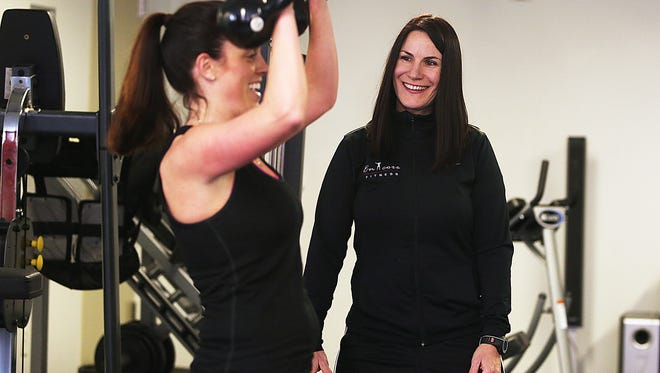 Tracy Gannaway works with client Kelly Starbuck at Encore Fitness in 2014.