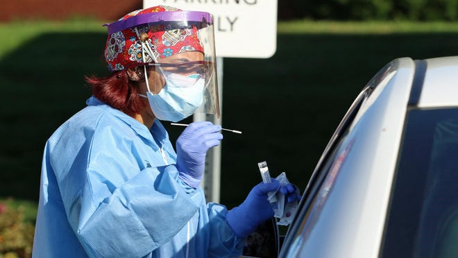 Registered nurse Mi'Chelle Johnson prepares to give a COVID-19 test to a person in a waiting car at the mobile testing site at Atrium Health Urgent Care on Robinwood Road Tuesday morning, Oct. 20, 2020.