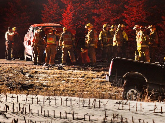 Sauk Rapids firefighters and other emergency personnel work at the scene of a head-on collision involving two pickup trucks Monday night near the intersection of Benton County Road 33 and 57 northeast of Sauk Rapids.