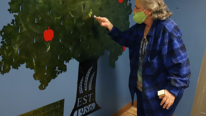 Wanda Osman of Advanced Welding in Rudy does a little touch-up work on the Giving Tree in River Valley Regional Food Bank's lobby Thursday, Nov. 5, 2020. Advanced Welding donated the steel tree that was cut on the company's CNC Plasma cutter from a piece of 10-gauge steel. The tree displays red and gold apples noting donations of $500 and $1000.