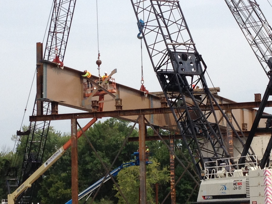Construction crews lay the beams for the bridge over the Grand River ...