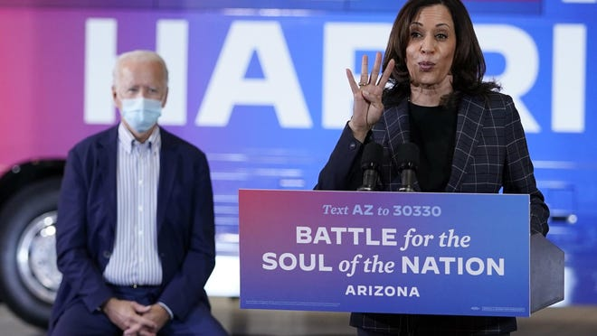 Democratic presidential candidate former Vice President Joe Biden listens as Democratic vice presidential candidate Sen. Kamala Harris, D-Calif., speaks at Carpenters Local Union 1912 in Phoenix Thursday to kick off a small-business bus tour.