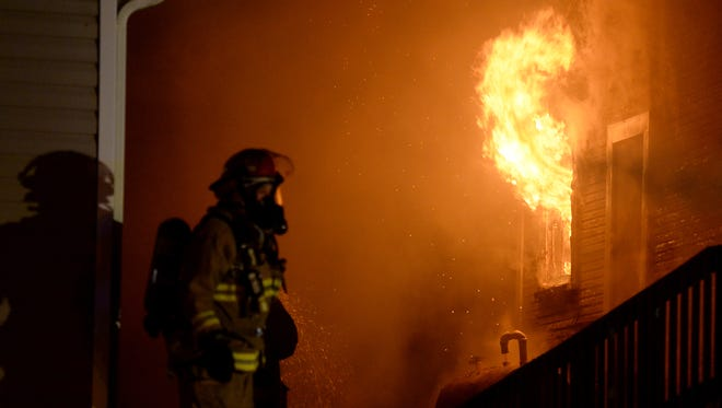 Fire fighters work to extinguish a fire at 412 N. 14th Street Friday, Jan. 22, 2016 in Richmond.