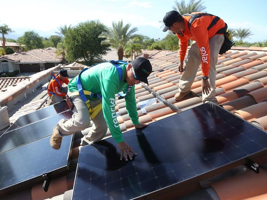Renova Solar installer leader Ralo Medina, center, installer Pablo Salazar, left, and installer Brandon Gomez, right, attach new panels to a rail system as the crew installs 8,000 watts of solar panel power at a home in Indian Ridge Country Club in Palm Desert in 2014.
