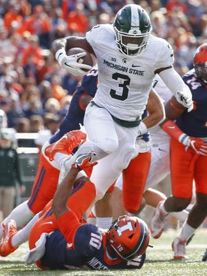 LJ Scott of the Michigan State Spartans runs the ball as Hardy Nickerson of the Illinois Fighting Illini attempts the tackle Nov. 5, 2016 in Champaign, Illinois.