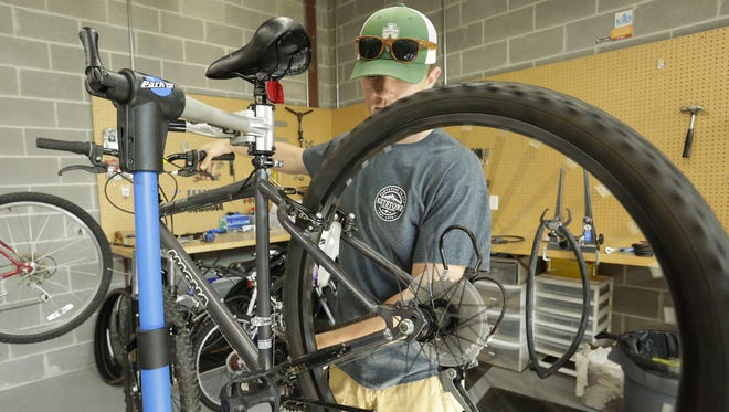 University of Wisconsin-Oshkosh bike shop student manager Ryan Ruffing works on a bike Tuesday, Sept. 19, 2017. The university's bike share program which started in 2012, has about 35 rental bikes for students. Short-term rentals and mountain bikes also are available. The program is supported by student segregated fees and is managed by students.