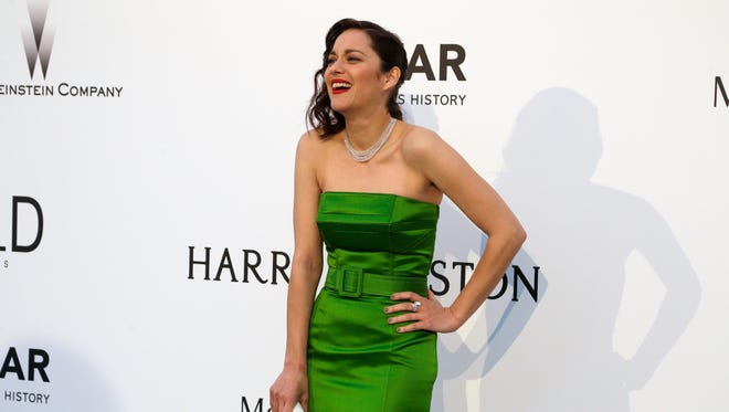 Actress Marion Cotillard laughs as she poses for photographers upon arrival for the amfAR Cinema Against AIDS benefit at the Hotel du Cap-Eden-Roc, during the 68th Cannes international film festival, Cap d'Antibes, southern France, Thursday, May 21, 2015.