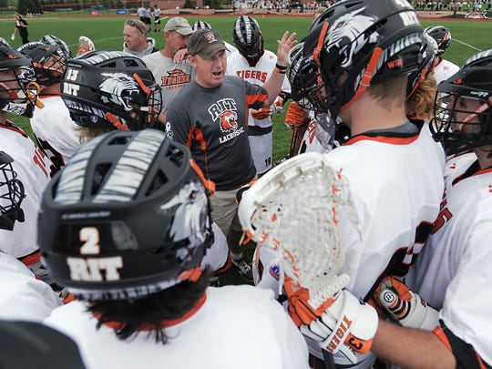 RIT head coach Jake Coon, center, huddles with his team in between quarters during a semifinal of NCAA DIII Men's Lacrosse Championships played at RIT's Tiger Stadium on Sunday, May 18, 2014. #6 Tufts University beat #1 RIT, 21-11 to advance to next week's championship game.